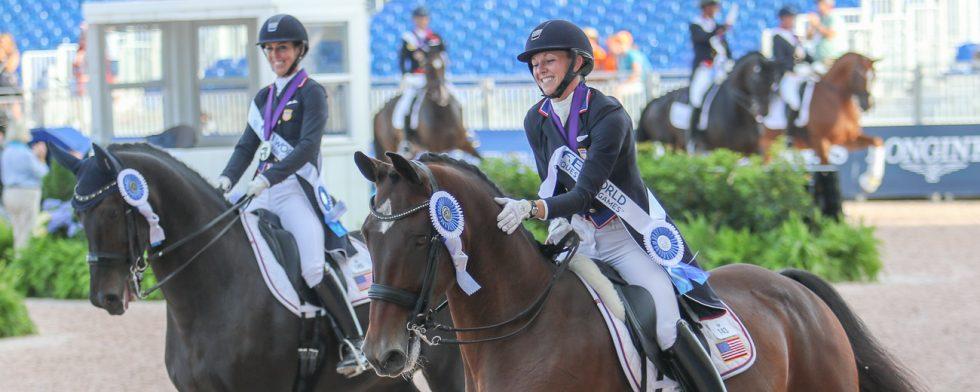 Laura Graves och Verdades firar en VM-silvermedalj i lag, bakom lagkamraten Kasey Perry Glass på Görklintgaards Dublet. Foto: Kim C Lundin