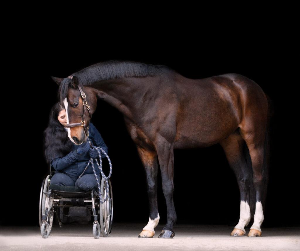 En flicka i rullstol sitter bredvid en brun häst.